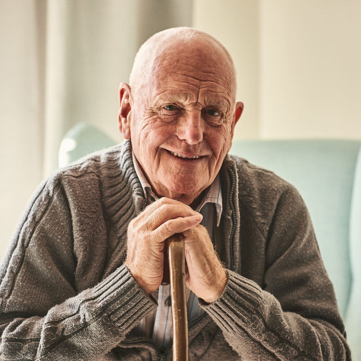 Portrait of happy senior man sitting at home with walking stock and smiling